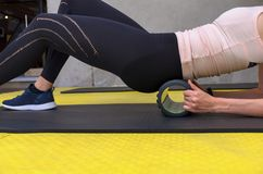 Close up view of woman exercising with foam roller stock photo