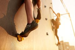 Close up view of woman feet in climbing shoes on artificial rock wall on sunset. Two active sporty women compete on. Bottom view of two young climbers Stock Image