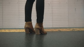 Close-up view of woman foot wearing shoes in subway platform. Girl standing near restrictive line and waiting train. Close-up view of woman foot wearing height stock video