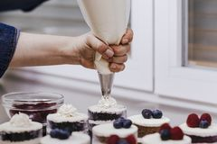 Close up view of woman hand cutting nuts with knife and adding them into a bowl for a recipe. bakery concept.  royalty free stock image
