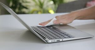 Close up view of woman hand using antibacterial wet wipe for disinfecting laptop