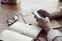 Close-up view of woman hands with phone and note pad, glasses, in cafe. Close-up view of woman hands with phone and note pad, glasses Royalty Free Stock Photos