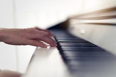 Close up view of woman hands playing electronic piano at home. stock image
