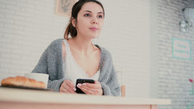 Close-up view of woman having breakfast and browsing Internet, using touchscreen. Girl read new on smartphone and smile. Stock Photo