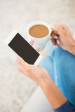 Close up view of a woman holding coffee and smartphone. At home Stock Photo