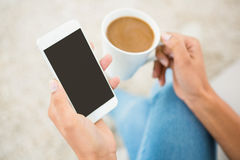 Close up view of a woman holding coffee and smartphone. At home Royalty Free Stock Photos