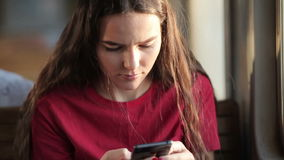 Close-up view of woman holding smartphone. Sitting in public transport. Girl types a message stock video footage