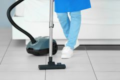 Close up view of woman hoovering floor Stock Photo