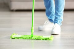 Close up view of woman moping. Floor at home Stock Photos