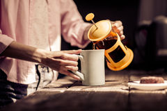 Close up view of woman pouring tea in white cup. Royalty Free Stock Photos
