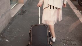Close-up view of woman s leg walking on the sidewalk carrying the suitcase. Girl arrives and explores the neighborhood. Close-up view of woman s leg in sneakers stock video