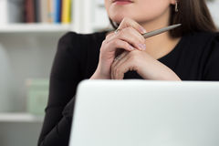 Close up view of woman sitting at laptop, holding pen and thinki Royalty Free Stock Image