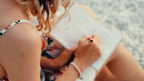 Close up view of woman writing in her diary at sunset sitting on the beach stock video footage