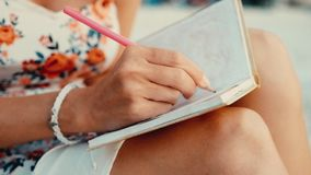 Close up view of woman writing in her diary at sunset sitting on the beach stock footage