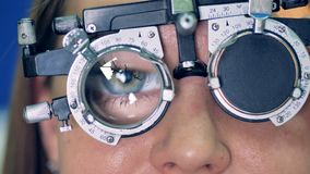 A close-up view on a womans eye behind the optical trial frame. A blinking female eye behind an optical trial frame during a clinical test with several lenses stock video footage