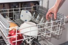 Close up view of a woman's hand loading the dishwasher. Shallo Royalty Free Stock Photography