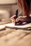 Close up view of womans hand writing in notebook. Royalty Free Stock Photo