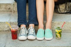 Women`s feet in sneakers on stairs. Close up view of women`s feet in blue sneakers relaxing on stairs with cocktails Royalty Free Stock Photo