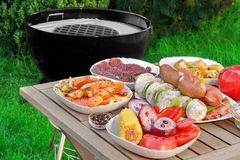 Close-up View On Wood Picnic Table  With Different Cookout Food. For Summer BBQ Family Party On The Backyard And Empty Barbecue Grill Appliance On The Green Royalty Free Stock Photo