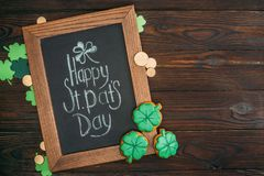 Close-up view of wooden frame with happy st patricks day inscription and golden coins. On table stock illustration