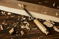 Close up view of wooden plank and pieces with chisel on brown table stock photos