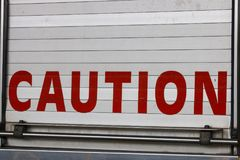 A Caution Sign. A close up view of the word caution in red on the back of a fire engen stock images