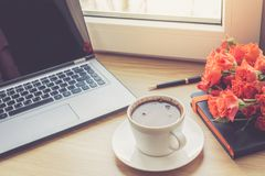 Work desk interior with a laptop computer and morning coffee cup. Toned photo of female work desk with computer and coffee cup. Close up view on work desk Royalty Free Stock Image