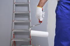 Close up view of worker with paint roller. In room Royalty Free Stock Images