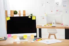 Close up view of workplace with blank computer screen, sticky notes and papers. In office stock photography