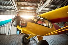 Single-engine propeller airplane standing in hangar with opened motor cabinet. Close up view of yellow single-engine propeller airplane standing in hangar royalty free stock images