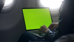 Busy woman writing email text on laptop in airplane stock video