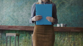 Close-up view of young blonde female holding the documents. Woman manager working in modern trendy office. Close-up view of young blonde female holding the stock video