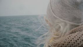 Close-up view of young blonde woman traveling on ship. Attractive female looking on sea and waves, hair waving on wind. Close-up view of young blonde woman stock video footage