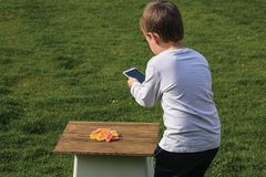 Close up view of a young boy taking picture of candies on his mobile. royalty free stock image