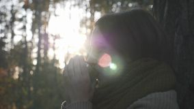 Close up view of young brunette woman drinking hot tea in autumn park. Female traveler drinking coffee from thermos at nature.  stock video footage