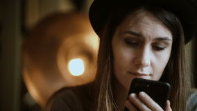 Close-up view of young brunette woman holding the smartphone and typing the message on touchscreen sitting in cafe. Attractive female spending leisure time in stock video footage
