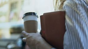 Close-up view of young businesswoman holding documents, notebooks and coffee, going to work in office. Slow motion. Busy female manager walking through the stock footage