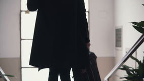 Close-up view of young businesswoman with suitcase. Traveler girl comes downstairs on ladder with baggage. stock video footage