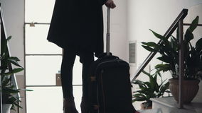 Close-up view of young businesswoman with suitcase. Traveler girl comes downstairs on ladder with baggage. Stock Photography