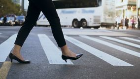 Close-up view of young businesswoman wearing shoes with heels crossing the road in busy downtown. Slow motion. stock video