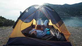 Close-up view of young couple`s legs lying in camping tent with feet joined while resting after hiking day. Happy lovers. Enjoying beautiful sea view and stock video footage