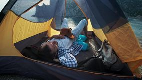 Close-up view of young couple`s legs lying in camping tent with feet joined while resting after hiking day. Happy lovers. Enjoying beautiful sea view and stock video