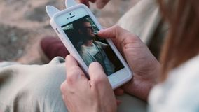 Close-up view of young couple sitting on the beach, on the sand and looking photos on smartphone, using touchscreen. Romantic date of man and woman on the stock video footage