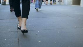 Close-up view of young female walking through the downtown. Businesswoman wearing black shoes with heels. Slow motion. stock footage