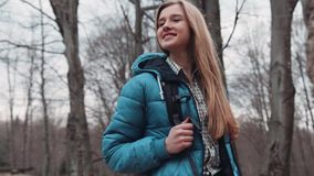 Close up view of young gorgeous tourist girl with a backpack carelessly wondering in the autumn forest. Autumn season. Fallen leaves around. High rocks. Active stock video footage