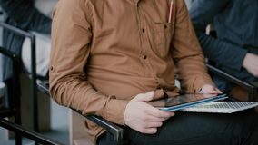 Close-up view of young man with notebook and digital tablet sitting on chair. Male at seminar or lecture at university. stock video