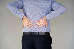 Businessman pain at lower back. Close-up view of a young man with pain in kidneys on gray background. Businessman with back ache clasping her hand to her lower Stock Photography
