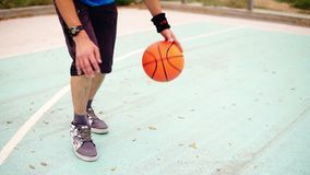 Close up view of a young man practicing basketball outside. Slowmotion shot stock video footage