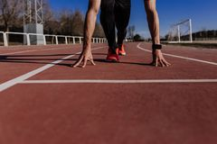 Close up view of young muscular athlete is at the start of the race tracks line at the stadium. Sports concept royalty free stock photography