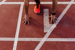 Close up view of young muscular athlete is at the start of the race tracks line at the stadium. Sports concept.  stock photos